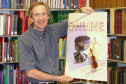 John Cuthbert, curator with the WVU Libraries\' West Virginia and Regional History Collection, shows the poster that will be handed out during West Virginia Day celebrations today (June 20) at Eliza\'s coffee shop in the Dowtown Campus Library.