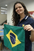 WVU student Livia Cascao shows the flag of her home country, Brazil. Cascao swam competitively on the Mountaineer Women\'s Swimming Team for four years and also mastered English while at WVU.