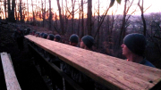 ROTC Cadets preparing to drop bridge beam into position from deck of existing bridge.